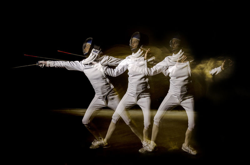 Multiple Image Of Female Athlete Fencing Against Black Background