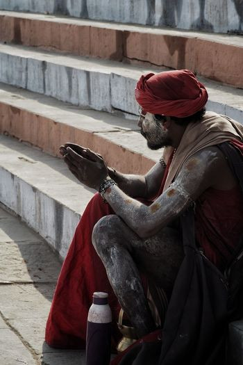 Close-up of sadhu sitting on staircase