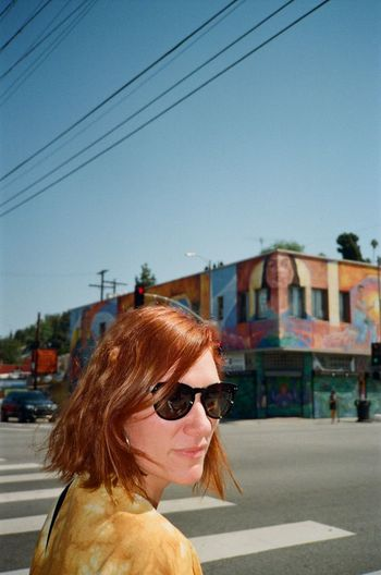 Portrait of young woman with sunglasses against sky in city