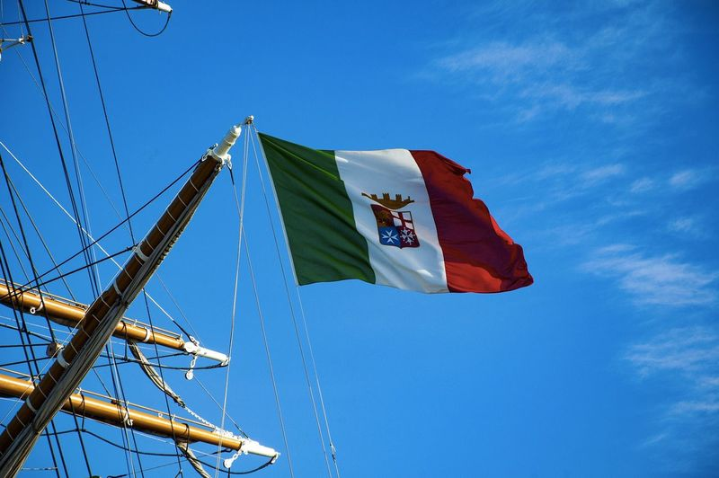 Low angle view of italian flag on tall ship against blue sky
