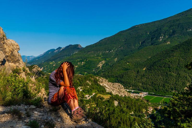 Full length of woman sitting against mountain range