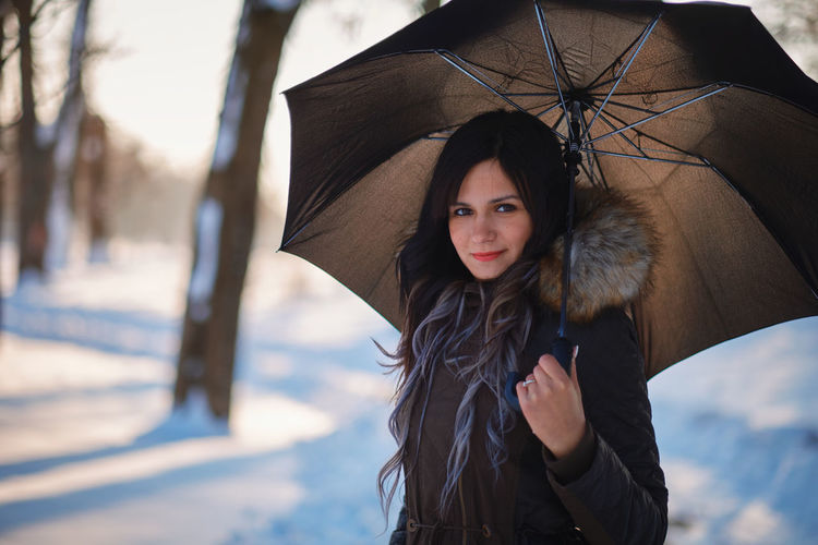 Portrait of woman holding umbrella while standing on outdoors during winter