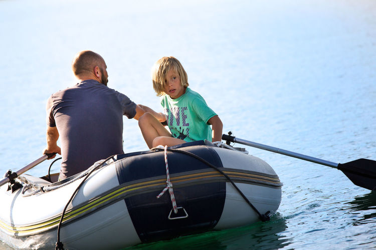 Father and son traveling in boat on sea