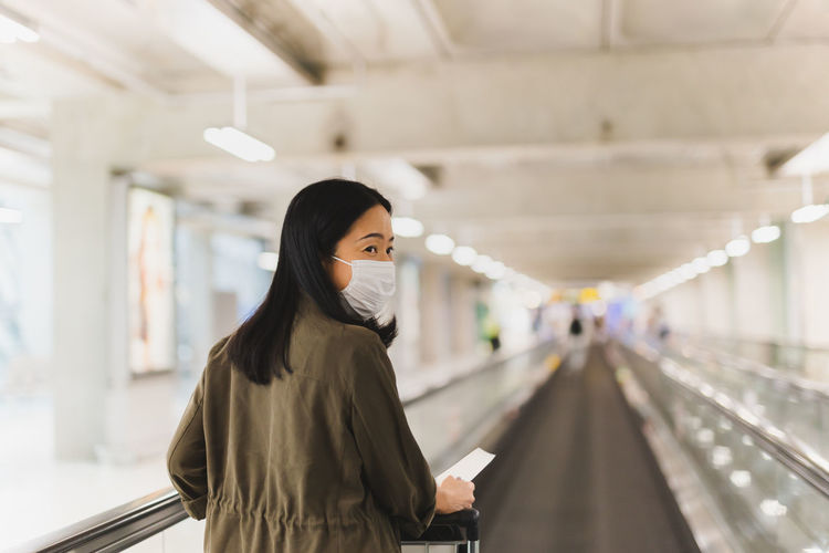 Woman passenger holding boarding pass ticket walking on escalator with trolley