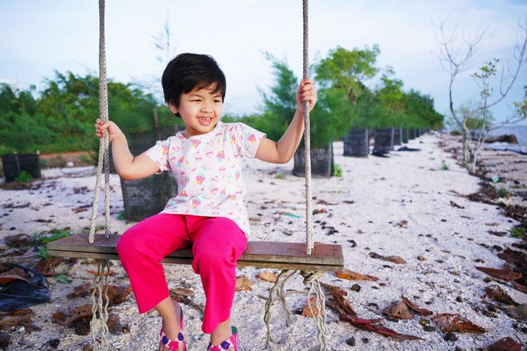 A girl is rocking in a tree on the beach