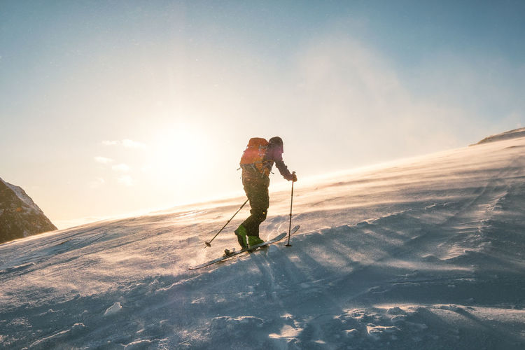 Man skiing on mountain against sky during winter