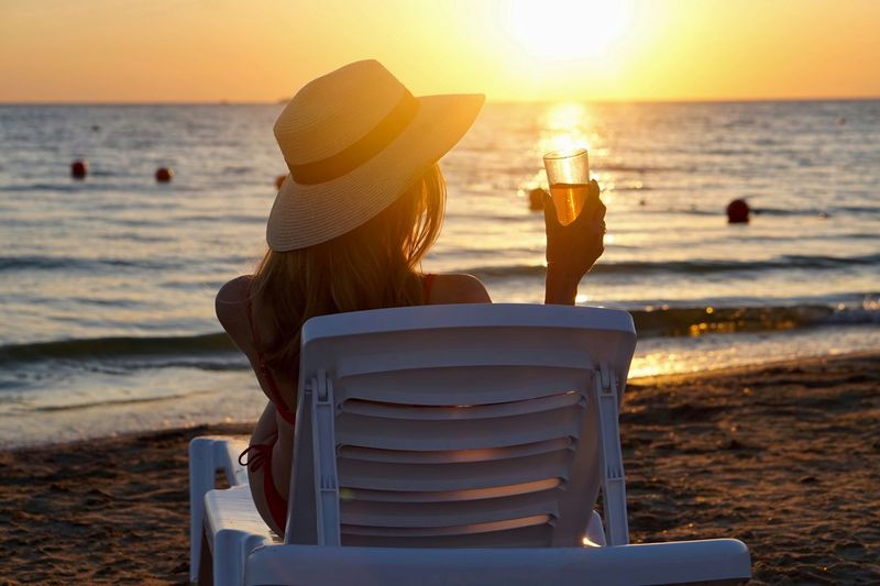 Rear view of woman holding drink glass on lounge chair at beach during sunset