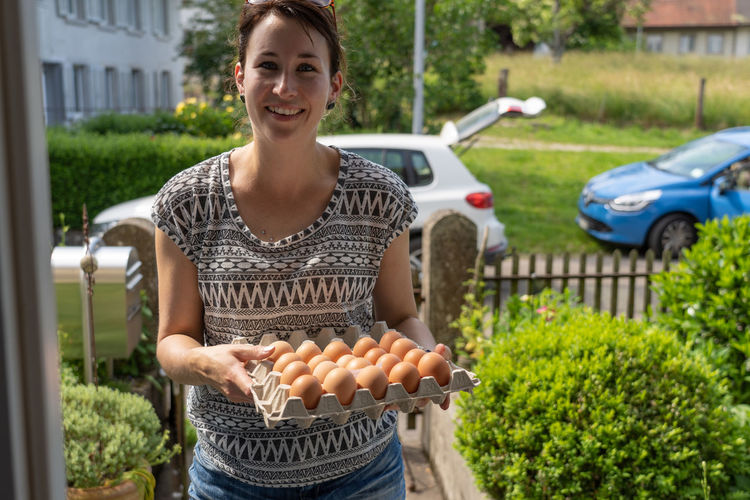 Portrait of smiling young woman selling eggs for small business