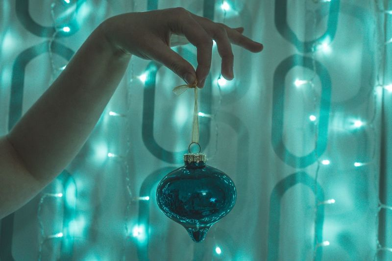 Cropped Hand Of Woman Holding Christmas Decoration Against Illuminated Lights