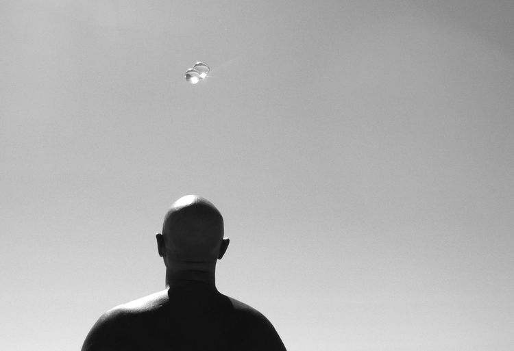 Rear view of bald man with crystal balls against clear sky