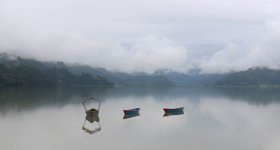 Boats in lake against cloudy sky