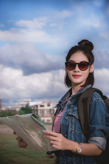 Portrait of young woman wearing sunglasses while holding map against sky