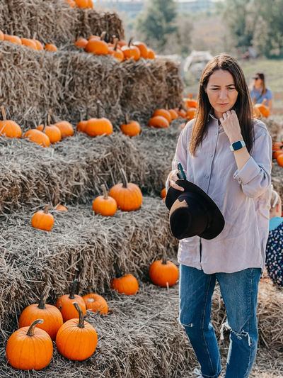 Full length of woman standing by pumpkins