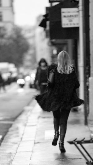 Rear view of women walking on sidewalk