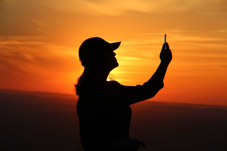 Silhouette woman taking selfie against orange sky during sunset