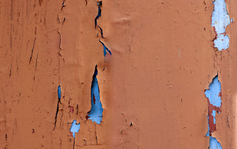 Paint that is cracked on the wall,red rust primer,