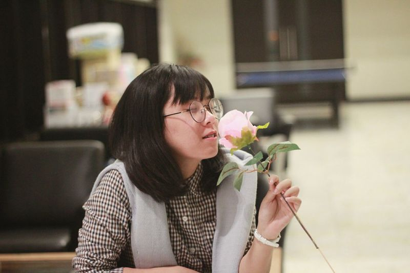 Young woman holding flower while sitting at home