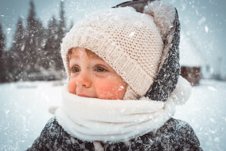 Close-up of boy crying in warm clothing during snowfall