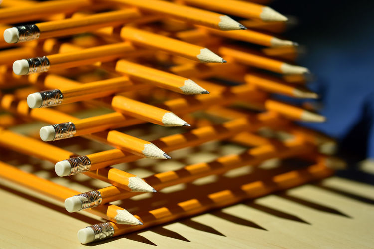 Close-up of stacked orange pencils on table
