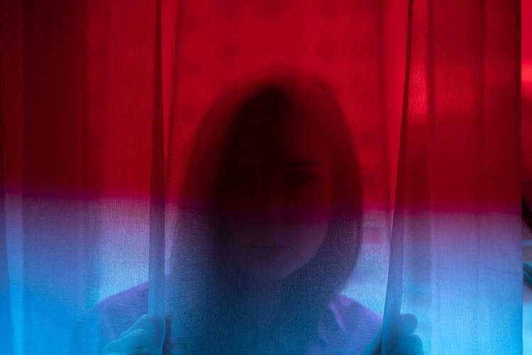 Digital composite image of woman against blue curtain