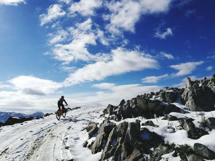 Rear view of man riding bicycle on snowcapped mountain against sky