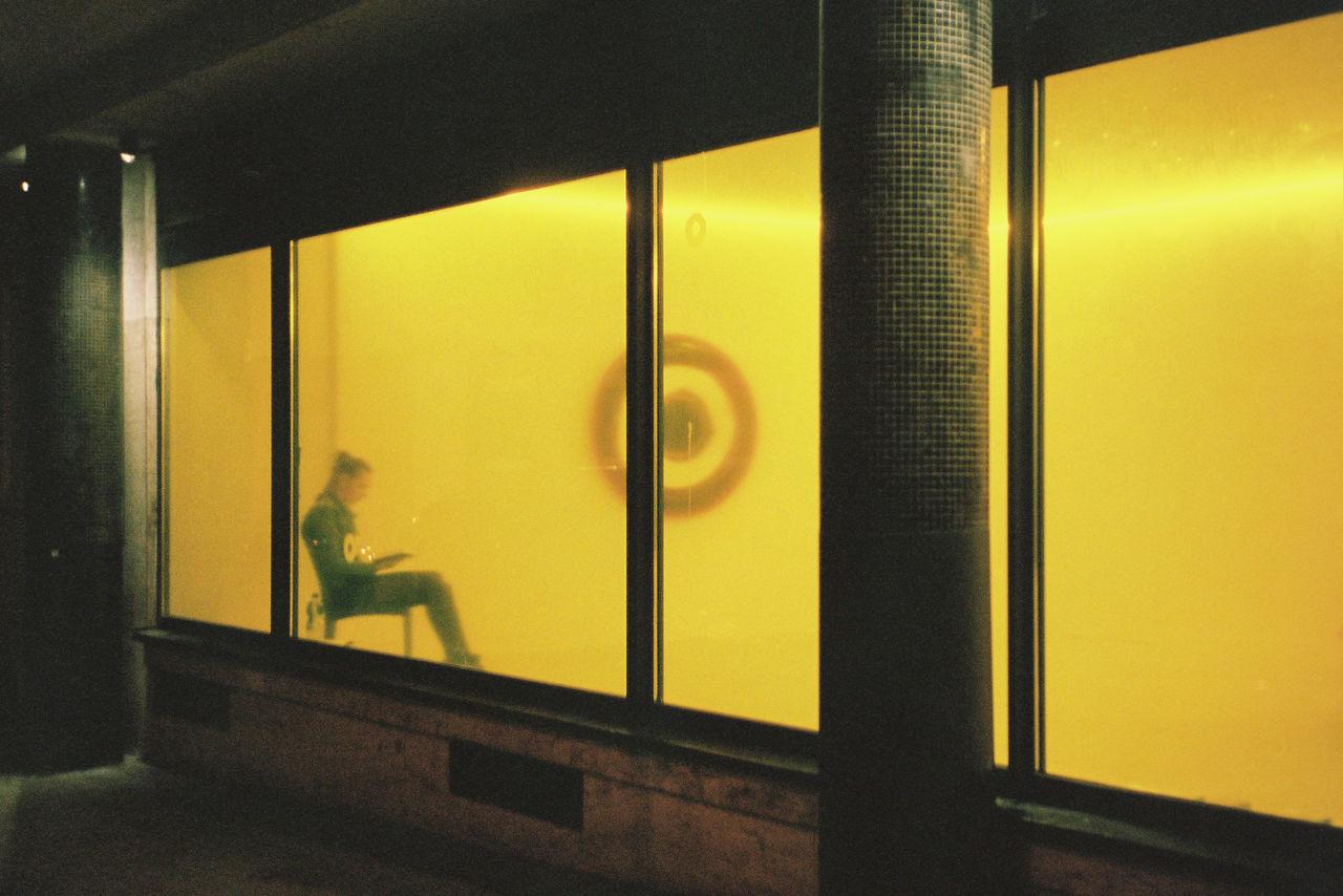 Side view of women seen through yellow window