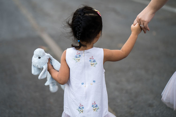 Girl holding dog doll walking at street with mum