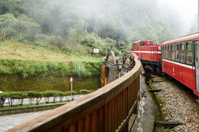 Travel by Train Red Train Train Tracks Train Train - Vehicle Travel Mountain Fog Forest Outdoors Red Tree Water Day Nature No People Sky