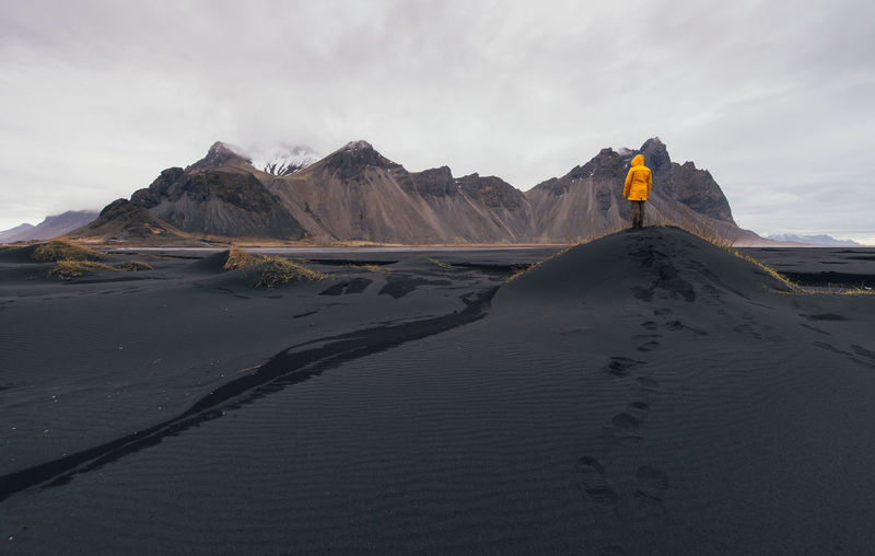 Man standing on black sand in desert
