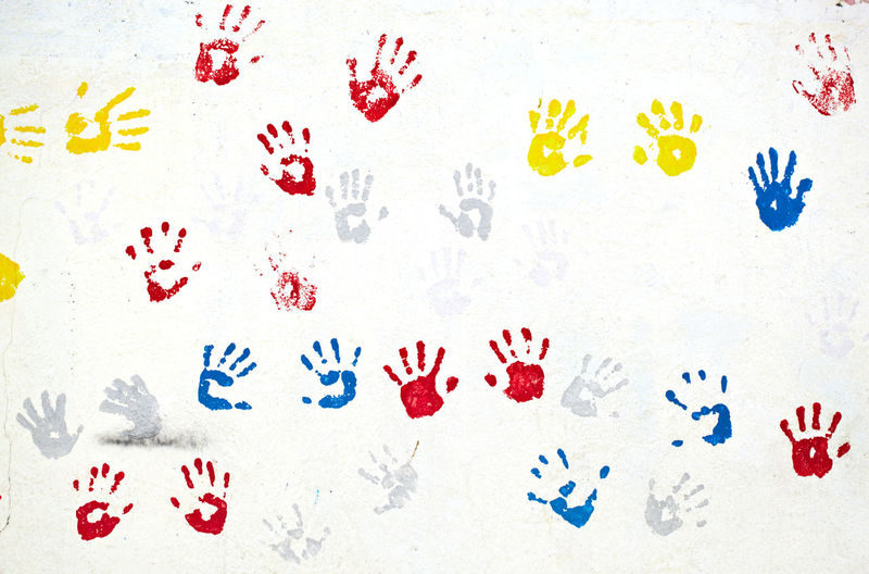 Close-up of colorful handprints on white wall