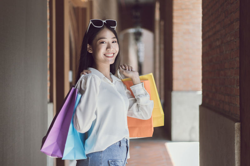 Smiling young woman holding shopping bag standing against wall