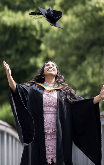 Smiling young woman throwing mortarboard