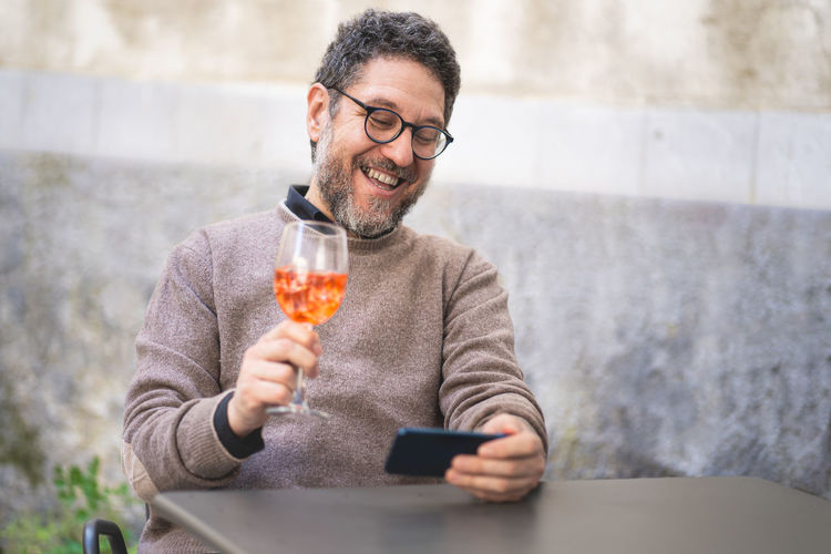 A middle-aged man toasts at a virtual party in a video call with a spritz during the quarantine