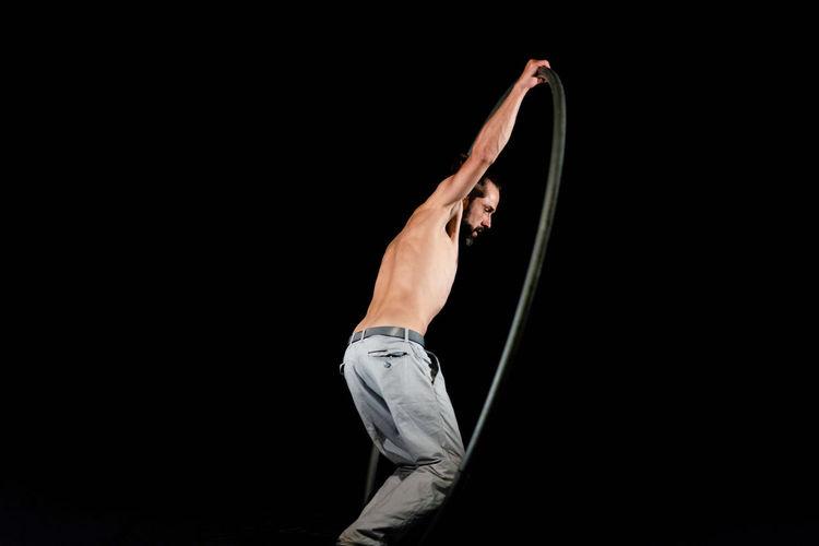 Circus Acrobat Adult Agility Arms Raised Balance Black Background Effort Exercising Flexibility Gymnastics Healthy Lifestyle Human Arm Human Body Part Human Limb Indoors  Limb Men One Person Performance Skill  Sport Strength Studio Shot Vitality