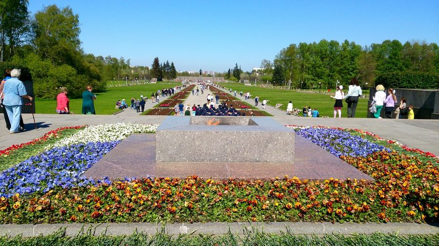 People at piskaryovskoye memorial cemetery against clear sky on sunny day