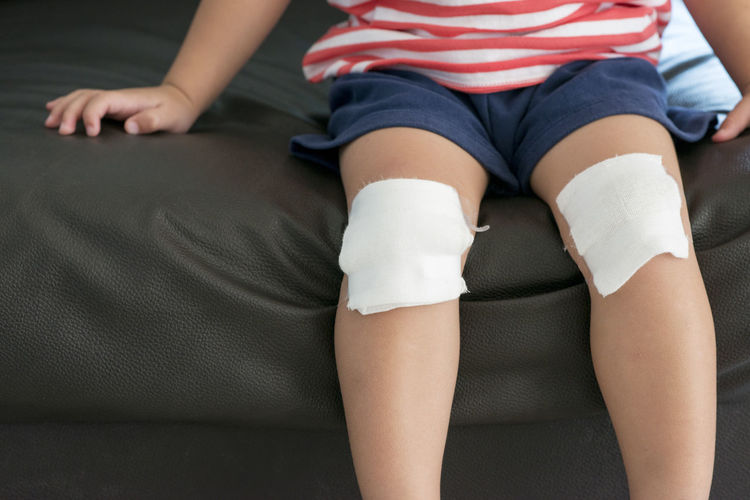 Midsection Of Boy Sitting On Sofa With Bandage On Knees