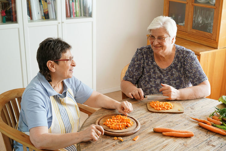 Two senior ladies cooking together. Cuting vegetables itting down at a large wood table. Cooking Authentic Casual Clothing Caucasian Cheerful Cutting Board Domestic Life Domestic Room Eyeglasses  Food Food And Drink Gray Hair Happiness Home Interior Indoors  Lifestyles People Preparation  Real People Senior Adult Senior Women Smiling Table Togetherness Two People