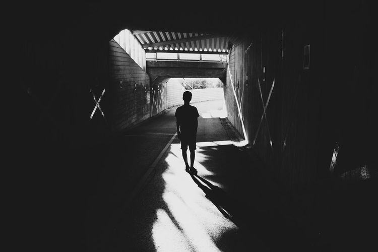 Full Length Rear View Of Silhouette Boy Standing In Covered Walkway