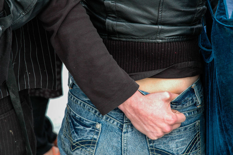 Midsection of person putting hand in woman jeans