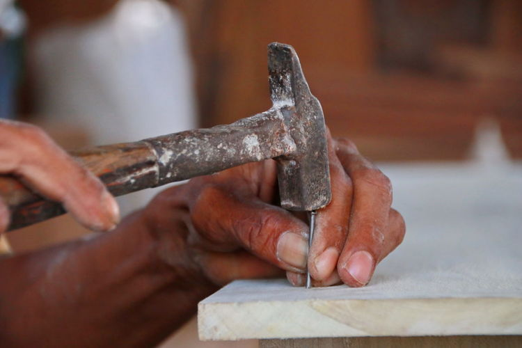 Cropped hand hammering nail on wooden plank