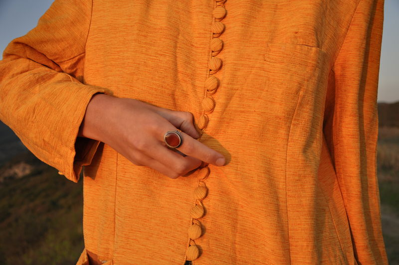 Midsection of woman buttoning orange traditional clothing