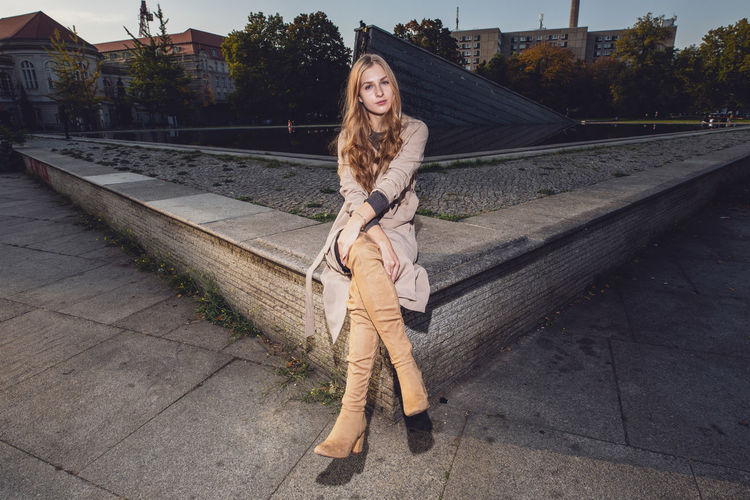 Young woman sitting on retaining wall in city