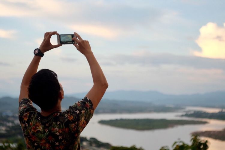 Rear view of man photographing while standing against sky during sunset