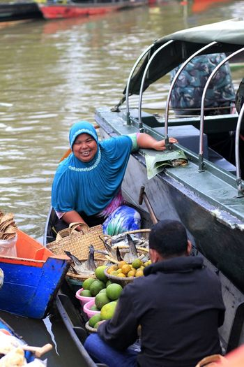 Portrait of smiling woman selling food on boat in lake