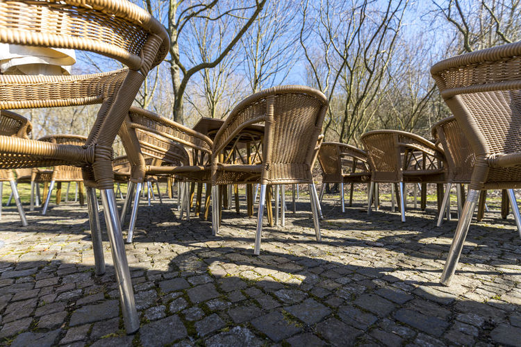 Empty chairs in park against sky