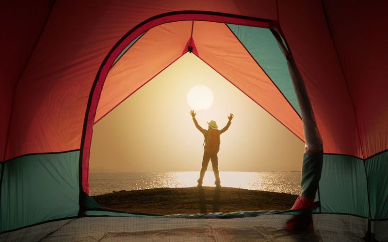 Tent view on window with man standing and open hand on sunset or sunrise background Tent View Man Sun Sunset Sunlight Sunrise Open Hand Sanding