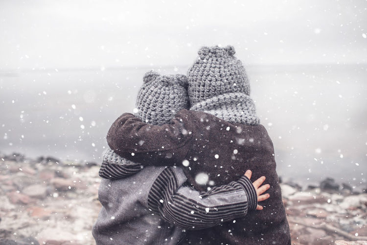 Rear view of sibling embracing while standing by lake during winter