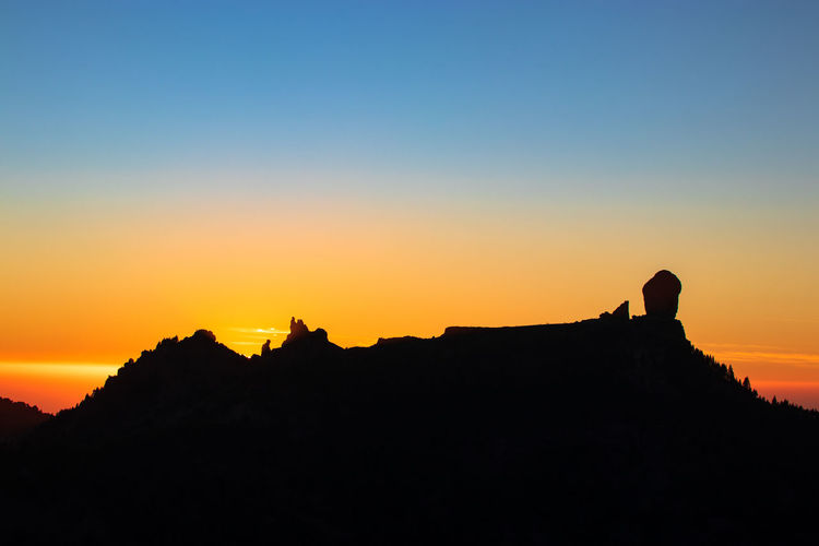 Silhouette mountain against clear sky during sunset