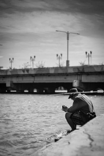 Man sitting on boat in river against sky