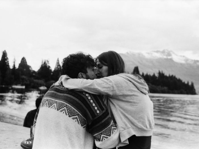Rear view of couple kissing against sky